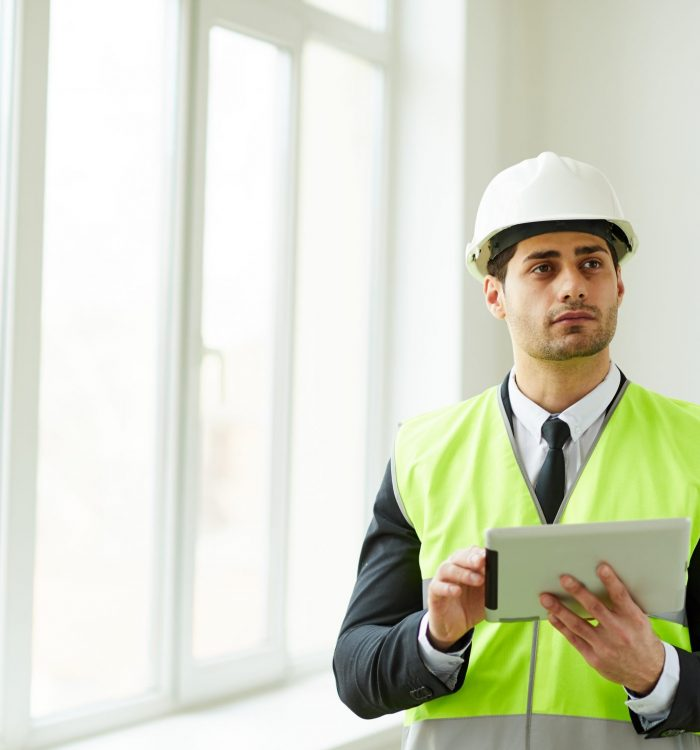 Waist up portrait of Middle-Eastern engineer wearing hardhat posing on construction site holding tablet, copy space